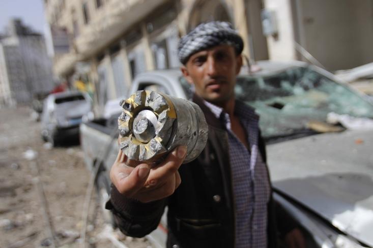 مرد یمنی تکه باقی مانده از موشک های سعودی را در دست گرفته است