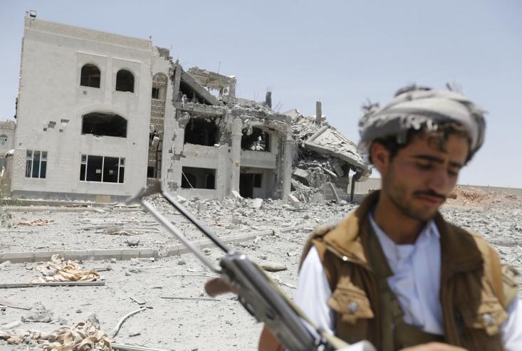 یک رزمنده انصارالله در مقابل ساختمان فرماندهی تخریب شده این گروه